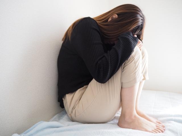 膝を抱えて顔を伏せる女性